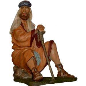 pastor sentado en roca con bastón